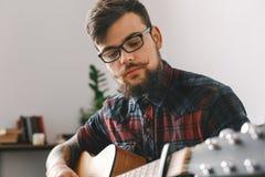 Giovani pantaloni a vita bassa del chitarrista a casa con la chitarra che gioca primo piano premuroso Immagine Stock