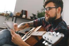 Giovani pantaloni a vita bassa del chitarrista a casa con melodia di seduta di scrittura della chitarra ispirata Immagini Stock