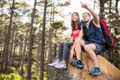 Giovani pareggiatori felici che si siedono sulla sensibilità della roccia e che indicano a qualcosa Fotografie Stock