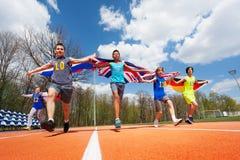 Giovani partecipanti multietnici della corsa con le bandiere Fotografia Stock Libera da Diritti