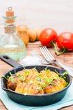 Giovani patate al forno in spezie e olio con la rucola in una pentola Immagine Stock