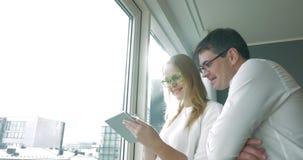 Giovani persone di affari felici con il cuscinetto dalla finestra stock footage
