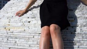 Giovani piede ed ente femminili alla moda alla moda in un possing nero del vestito all'aperto stock footage