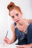 Giovani pitture dai capelli rossi della donna nel suo ozio Fotografia Stock