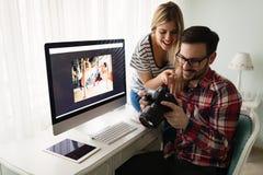 Giovani progettisti attraenti che lavorano insieme dalla casa Immagini Stock Libere da Diritti