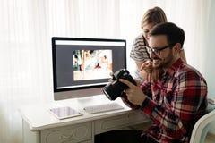 Giovani progettisti attraenti che lavorano insieme dalla casa Fotografie Stock