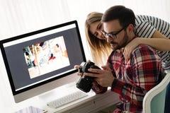 Giovani progettisti attraenti che lavorano insieme dalla casa Immagini Stock