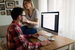 Giovani progettisti attraenti che lavorano insieme dalla casa Fotografia Stock
