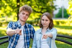 Giovani ragazza e ragazzo delle coppie di estate nel parco in natura Si siedono su un banco in città Gestures con il suo Fotografia Stock