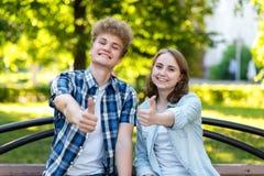 Giovani ragazza e ragazzo delle coppie Estate in parco su un banco Sorrisi felicemente Mani dure che mostrano i pollici su, come  Fotografie Stock Libere da Diritti