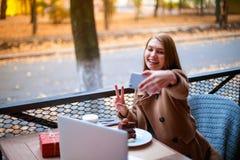 Giovani, ragazza in un caffè all'aperto che fa selfie Immagine Stock