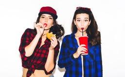 Giovani ragazze dei pantaloni a vita bassa divertendosi bevendo una soda da paglia e tenendo un hamburger, un sorriso felice e un fotografia stock