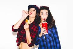 Giovani ragazze dei pantaloni a vita bassa divertendosi bevendo una soda da paglia e tenendo un hamburger, un sorriso felice e un immagine stock