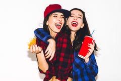 Giovani ragazze dei pantaloni a vita bassa divertendosi bevendo una soda da paglia e tenendo un hamburger, un sorriso felice e un immagine stock libera da diritti