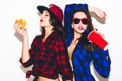 Giovani ragazze dei pantaloni a vita bassa divertendosi bevendo una soda da paglia e tenendo un hamburger, un sorriso felice e un fotografia stock libera da diritti