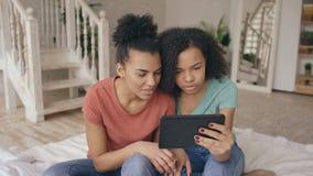 Giovani ragazze divertenti allegre della corsa mista che parlano sullo skype sul computer della compressa con i loro amici a casa stock footage