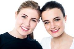 Giovani ragazze sorridenti che vi esaminano Fotografia Stock