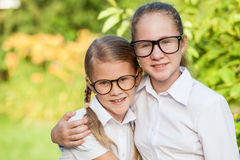 Giovani ragazze sorridenti della scuola in un uniforme scolastico contro un albero dentro Fotografia Stock