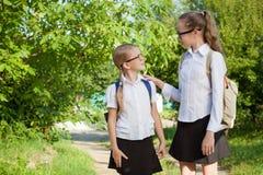 Giovani ragazze sorridenti della scuola in un uniforme scolastico contro un albero dentro Immagine Stock