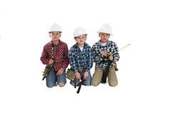 Giovani ragazzi che giocano in elmetti protettivi della costruzione Immagini Stock Libere da Diritti