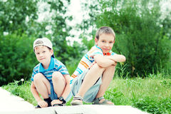 Giovani ragazzi che si siedono insieme e che sorridono Fotografie Stock Libere da Diritti