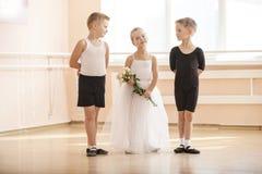 Giovani ragazzi e una ragazza con i fiori che posano con garbo Immagine Stock Libera da Diritti
