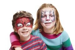 Giovani ragazzo e ragazza con il gatto e lo Spiderman della pittura del fronte Fotografia Stock Libera da Diritti