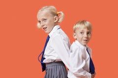 Giovani ragazzo e ragazza felici in uniforme scolastico che sta di nuovo alla parte posteriore sopra fondo arancio Fotografia Stock