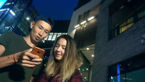 Giovani ragazzo ed amica asiatici felici delle coppie utilizzi uno smartphone mentre stanno su una via della città nella sera archivi video