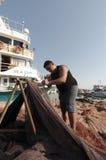Giovani reti dei pesci e del pescatore Fotografia Stock