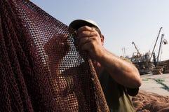 Giovani reti dei pesci e del pescatore Immagine Stock