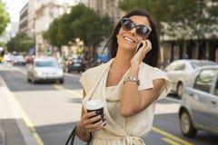 Giovani risate castane alla moda nel telefono Fotografia Stock