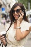 Giovani risate castane alla moda nel telefono Immagini Stock