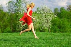 giovani rossi di salto della donna del prato inglese del vestito fotografie stock libere da diritti