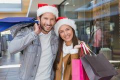 Giovani sacchetti della spesa felici della tenuta delle coppie con i cappelli di natale sui loro cappelli Fotografia Stock