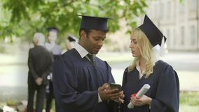 Giovani in schermo di sguardo uniforme del telefono del laureato, avendo discussione, lavoro stock footage