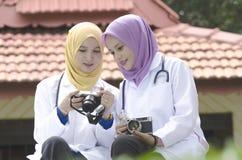 Giovani seduta e discussione di medico mentre tenendo la loro macchina fotografica al parco urbano Immagini Stock Libere da Diritti