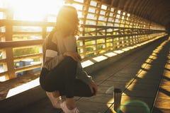Giovani seduta e resto castana snelli della ginnasta del ballerino della via della donna con la termo tazza sul ponte della via a fotografie stock libere da diritti