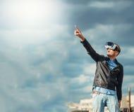 Giovani sicuri che indossano un paio dei vetri di VR che stanno sopra la città sulla costruzione del tetto con i precedenti del c Fotografie Stock Libere da Diritti