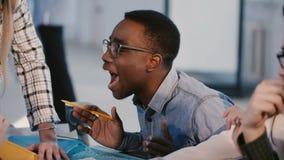 Giovani soci commerciali multietnici sorridenti felici che parlano, discutendo le idee del lavoro su 'brainstorming' dietro la ta stock footage