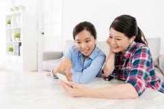Giovani sorelle eleganti che per mezzo del telefono cellulare mobile Fotografia Stock Libera da Diritti