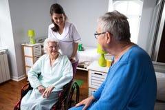 Giovani sorridenti di assistenza agli'anziani dell'infermiere fotografia stock