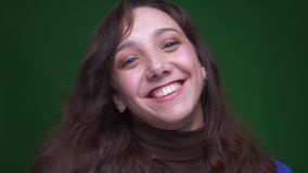 Giovani sorrisi castana della studentessa allegro che sono felici nella macchina fotografica su fondo verde video d archivio