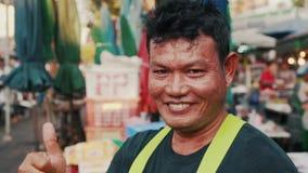Giovani sorrisi tailandesi dell'uomo nel mercato dell'alimento di notte video d archivio