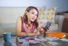 Giovani spese e reddito domestici di stima felici e soddisfatti di finanza della donna latina che sorridono facendo uso del calco immagini stock