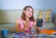 Giovani spese e reddito domestici di stima felici e soddisfatti di finanza della donna latina che sorridono facendo uso del calco fotografia stock libera da diritti