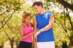 Giovani sport delle coppie che preparano il contatore di operazioni successive di Fitwatch di forma fisica Fotografia Stock