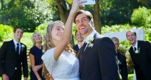 Giovani sposa felice e sposo che prendono selfie con la famiglia 4K 4k video d archivio