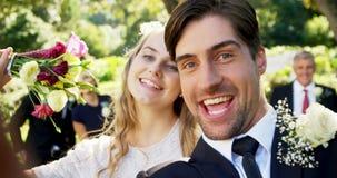 Giovani sposa felice e sposo che prendono selfie 4K 4k video d archivio