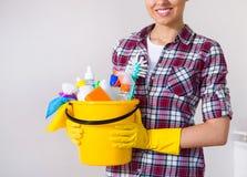 Giovani strumenti e prodotti graziosi di pulizia della tenuta della donna in secchio Immagini Stock Libere da Diritti